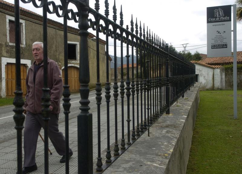 Ángel García Gómez pasa por delante de la verja de la Casa de Piedra, que alberga la Casa de Cultura de Colombres.