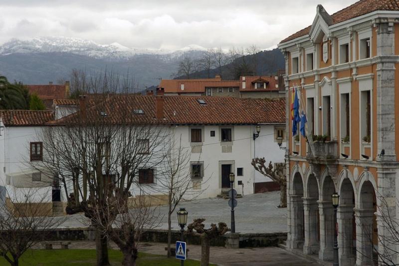 El edificio consistorial, con la sierra del Cuera nevada al fondo.