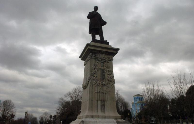 La estatua de Manuel Ibáñez Posada, en la plaza de Colombres que lleva su nombre, con la Quinta Guadalupe, sede del Archivo de Indianos, al fondo.